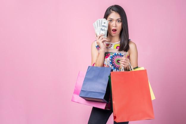 Retrato de mujer joven mostrando dinero con wow posó y llevando coloridas bolsas de compras