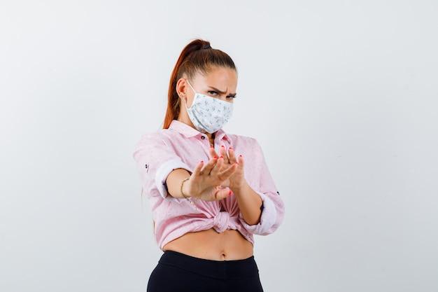 Retrato de mujer joven mostrando gesto de parada en camisa, pantalón, máscara médica y mirando asustado vista frontal