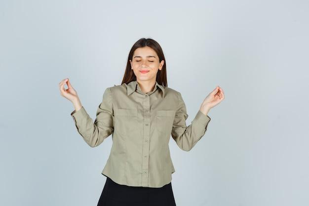 Retrato de mujer joven mostrando gesto de yoga con los ojos cerrados en camisa