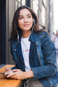 Retrato de una mujer joven en música que escucha de la chaqueta azul del dril de algodón en el auricular a través del teléfono móvil