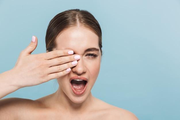 Retrato de una mujer joven muy emocionada posando aislada sobre la pared azul que cubre el ojo guiñando un ojo.