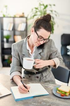 Retrato de mujer joven ocupada contestando llamadas telefónicas durante el almuerzo en la oficina