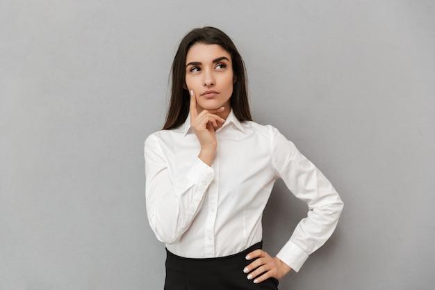 Retrato de mujer joven de oficina con mirada inquietante en camisa blanca mirando seriamente a un lado y sosteniendo el dedo en la mejilla, aislado sobre pared gris
