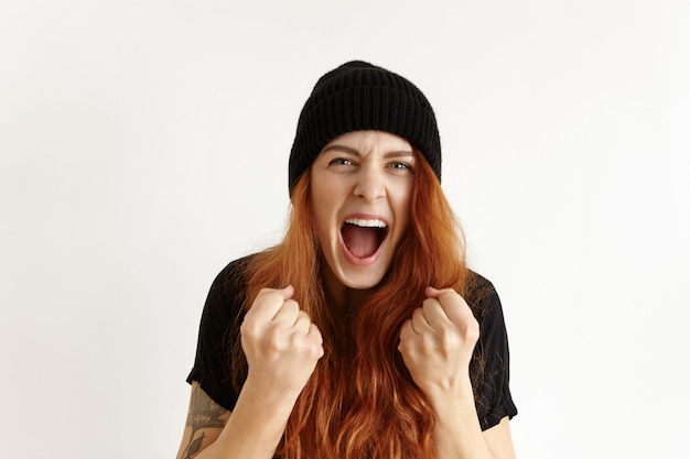 Retrato de mujer joven pelirroja enojada y furiosa con sombrero hipster expresando rabia e ira