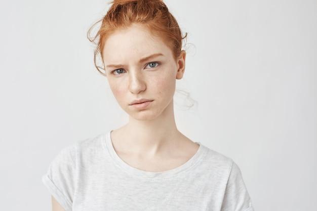 Retrato de mujer joven pelirroja tierna con piel sana pecosa vistiendo top gris con expresión seria.