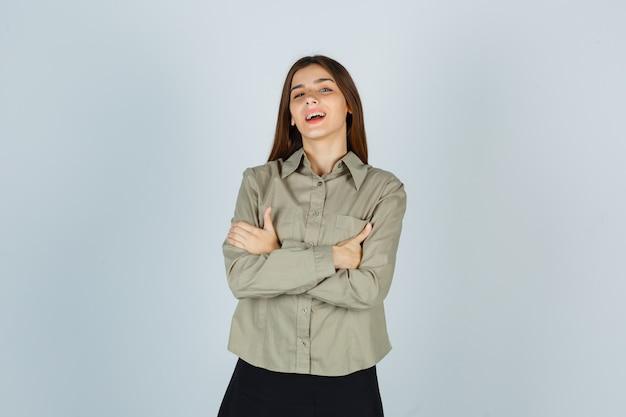 Retrato de mujer joven de pie con los brazos cruzados en camisa, falda y mirando feliz vista frontal