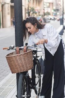 Retrato de mujer joven de pie cerca de la bicicleta en la calle