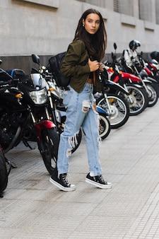 Retrato de una mujer joven de pie cerca de la bicicleta de estacionamiento en la acera