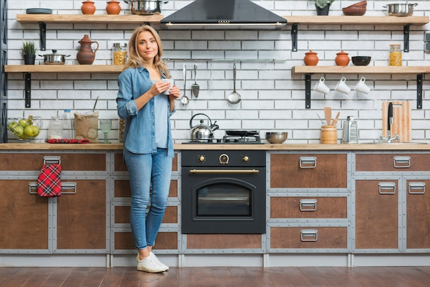Retrato de una mujer joven de pie cerca del mostrador de la cocina con una taza de café en la mano