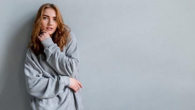 Retrato de una mujer joven de pie contra la pared gris