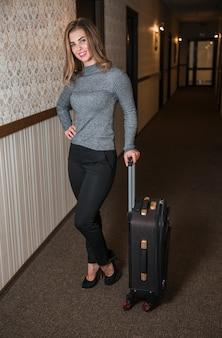 Retrato de una mujer joven de pie en el pasillo del hotel con la maleta