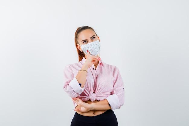 Retrato de mujer joven de pie en pose de pensamiento en camisa, pantalón, máscara médica y mirando pensativo vista frontal