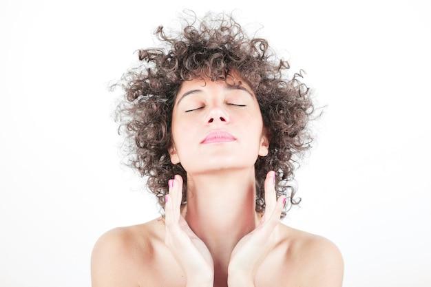 Retrato de mujer joven con la piel limpia y fresca y los ojos cerrados aislados sobre fondo blanco