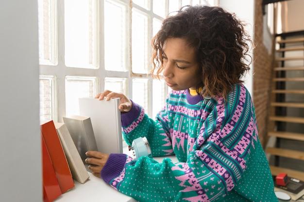 Retrato de una mujer joven de piel morena eligiendo un libro en casa.