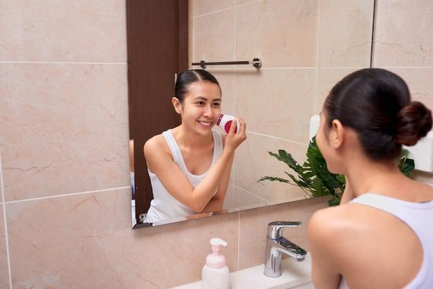 Retrato de mujer joven con una piel perfecta quitando el maquillaje con cepillo limpiador