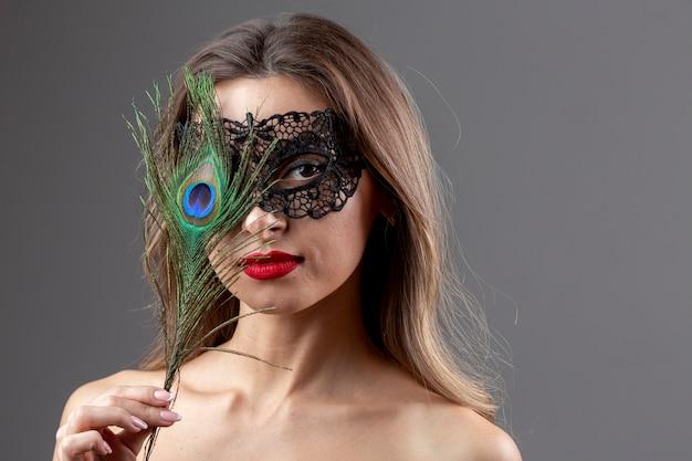 Retrato de mujer joven con plumas de pavo real