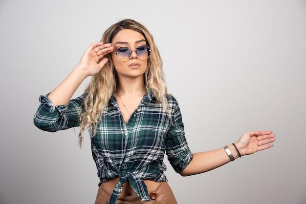 Retrato de mujer joven posando con gafas elegantes.