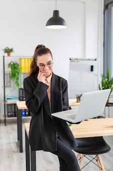 Retrato de mujer joven posando con laptop