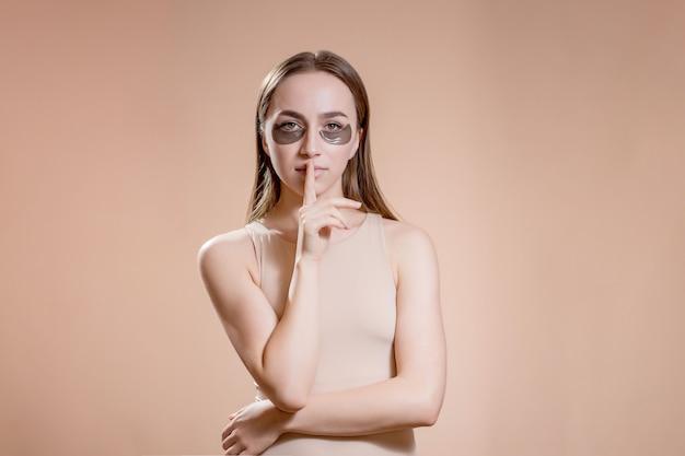 Retrato de mujer joven posando con parches de belleza negros aplicados debajo de los ojos sobre fondo beige.