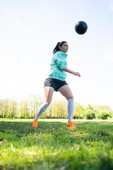 Retrato de mujer joven practicando habilidades futbolísticas y haciendo trucos con la pelota de fútbol