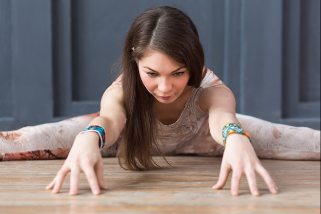 Retrato de mujer joven practicando yoga interior en pared gris urbano