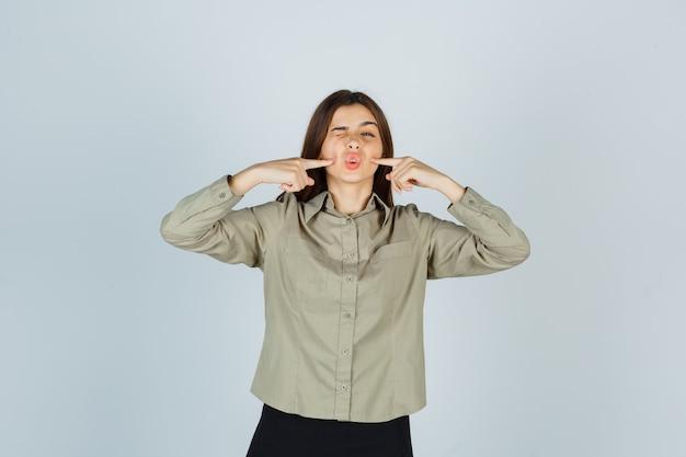 Retrato de mujer joven presionando los dedos en las mejillas mientras fruncía el ceño en camisa
