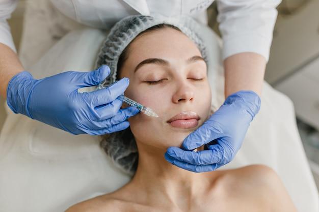 Retrato de mujer joven durante los procedimientos de cosmetología en salón de belleza. inyección, botox, manos en resplandores azules, salud, terapia, labios, belleza