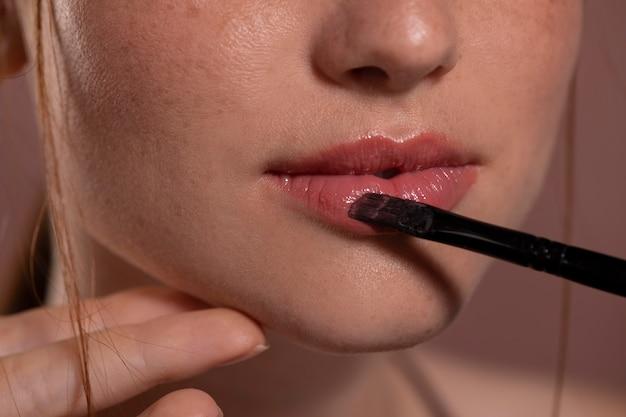 Retrato de mujer joven con un producto de maquillaje