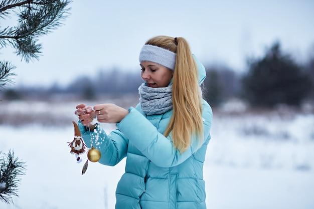 Retrato de mujer joven que adorna el árbol de navidad al aire libre. concepto de navidad e invierno.