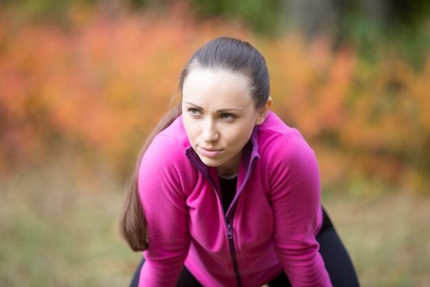Retrato de una mujer joven que calienta al aire libre en el otoño