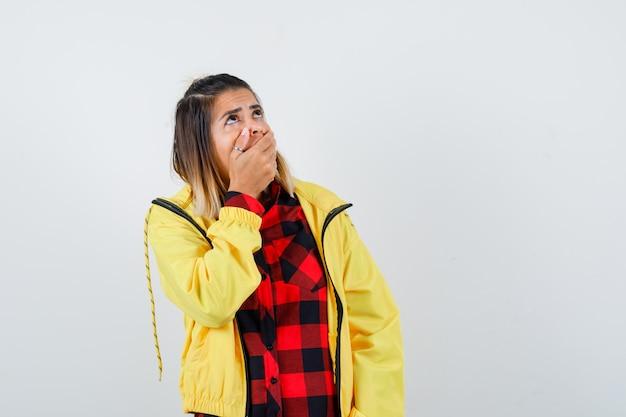 Retrato de mujer joven que cubre la boca con las manos, mirando hacia arriba con camisa a cuadros, chaqueta y mirando sorprendido vista frontal