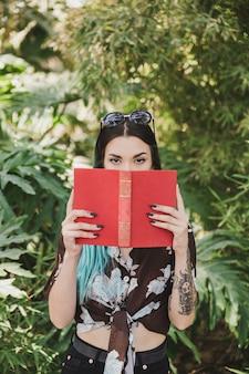 Retrato de una mujer joven que cubre su boca con libro rojo
