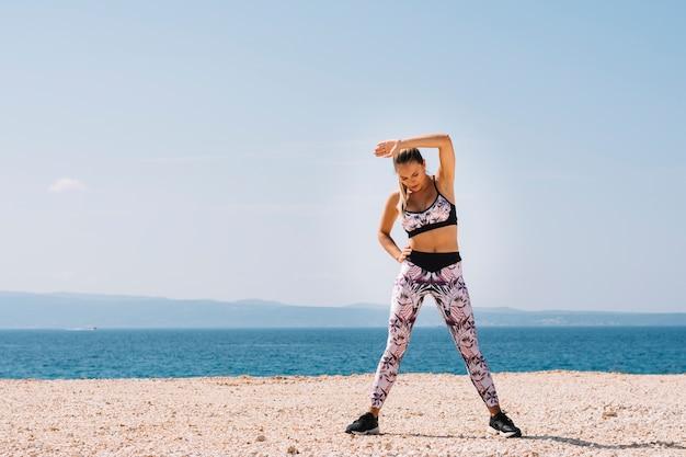 Retrato de una mujer joven que ejercita cerca de la playa