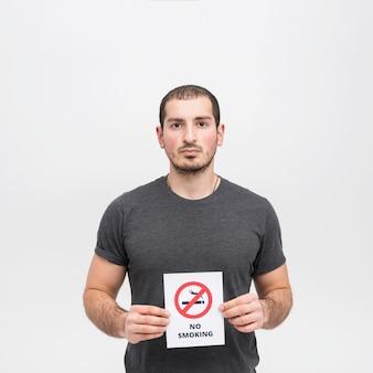 Retrato de una mujer joven que lleva a cabo la muestra de no fumadores contra el fondo blanco