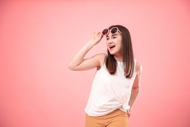 Retrato de una mujer joven que muestra emociones, con gafas en rosa aislado.