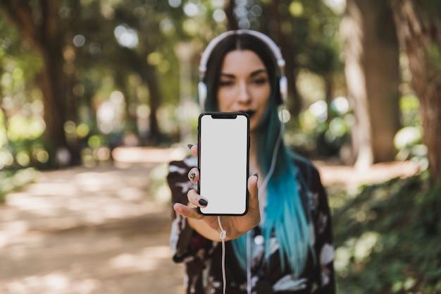 Retrato de la mujer joven que muestra el teléfono elegante blanco en blanco