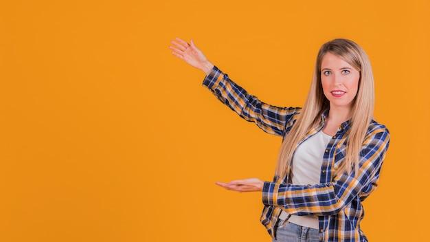 Retrato de una mujer joven que presenta algo sobre un fondo naranja