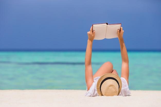 Retrato de una mujer joven que se relaja en la playa, leyendo un libro