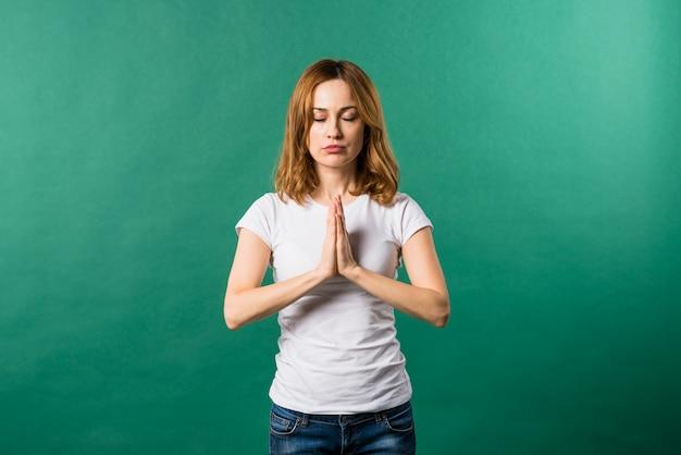 Retrato de una mujer joven que ruega contra fondo verde