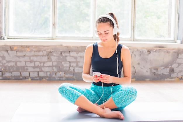Retrato de una mujer joven que se sienta en la estera del ejercicio usando el teléfono celular