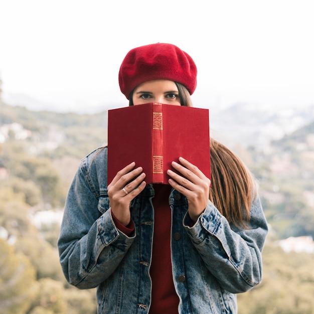 Retrato de una mujer joven que sostiene el libro rojo delante de su boca en el aire libre