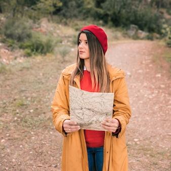 Retrato de una mujer joven que sostiene un mapa en la mano que se coloca en rastro