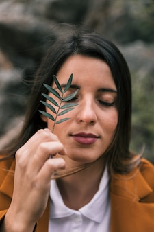 Retrato de una mujer joven que sostiene la ramita delante de sus ojos