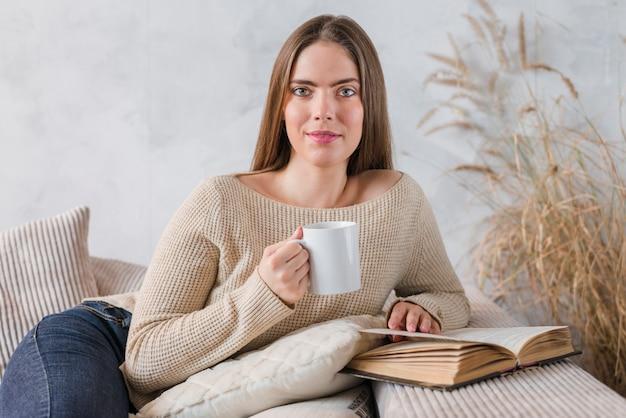 Retrato de una mujer joven que sostiene la taza de café que se sienta en el sofá con el libro