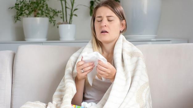 Retrato de mujer joven que sufre de alergia estornudos en un pañuelo de papel