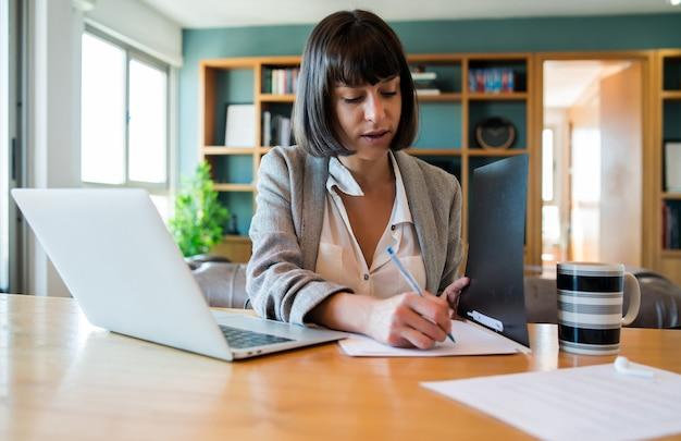 Retrato de mujer joven que trabaja desde casa con ordenador portátil y archivos. concepto de oficina en casa. nuevo estilo de vida normal.