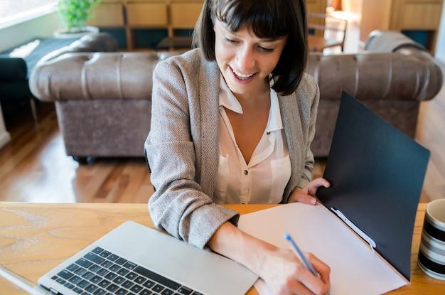 Retrato de mujer joven que trabaja desde casa con ordenador portátil y archivos. concepto de oficina en casa
