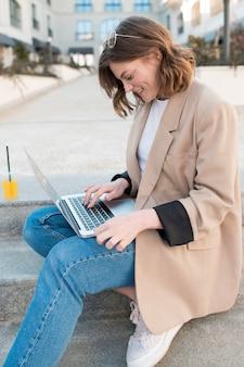 Retrato de mujer joven que trabaja en la computadora portátil