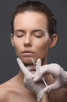 Retrato de mujer joven recibiendo inyección cosmética