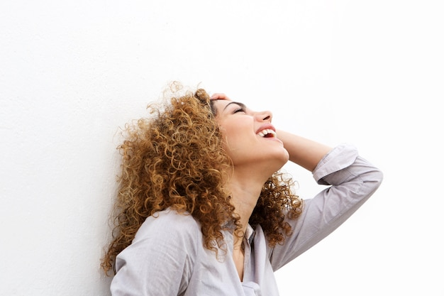 Retrato de mujer joven riendo con la mano en el pelo